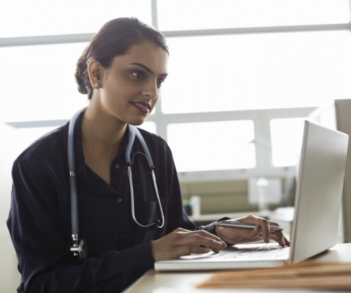 Doctor using laptop computer