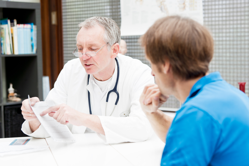 Doctor in white coat with stethoscope conducting appraisal with man in blue shirt