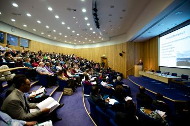 Large lecture hall containing several tiered rows of seated students