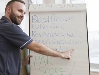 Man standing in front of flip chart pointing at key words, looking out towards the room