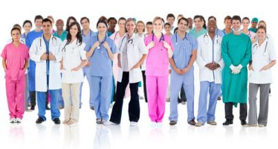 A large group of smiling doctors in blue, white and pink uniforms